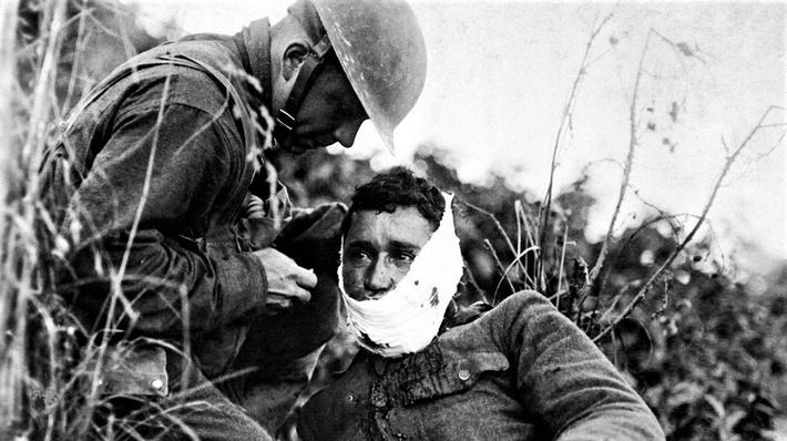 Photograph of a medic giving aid to an American soldier