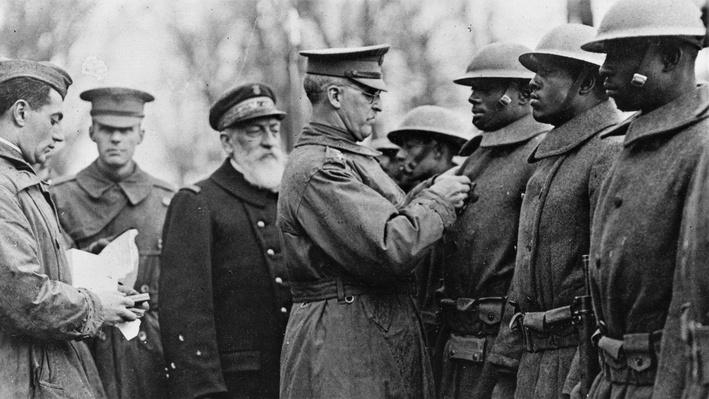 Photograph of General Pershing decorating african american soldiers with medals