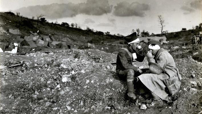 Photograph of two american soldiers taking a drink of water during battle