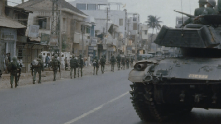Image of soldiers walking through a town, with a tank in the foreground.