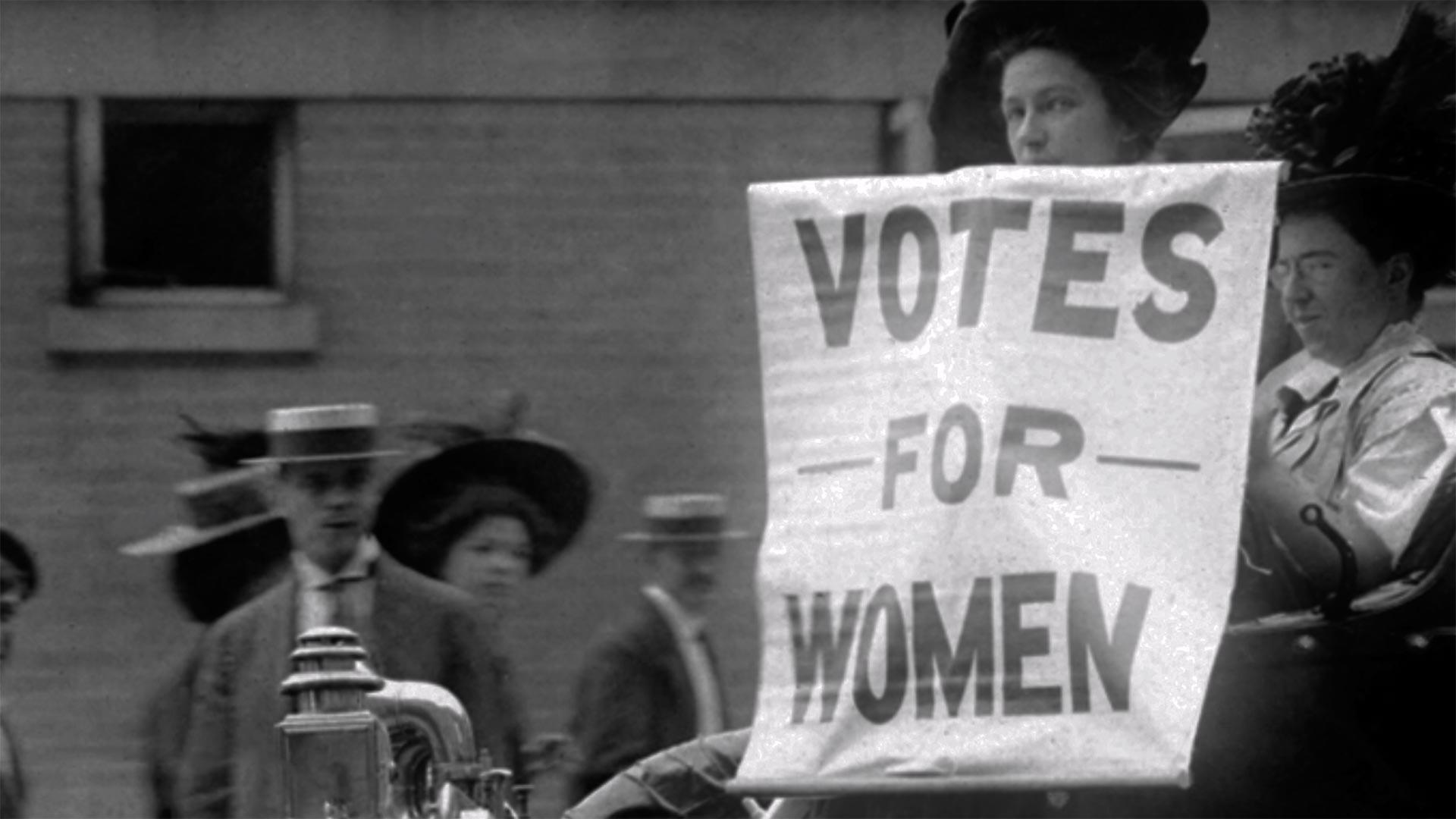 Woman holds up a Votes for Women sign
