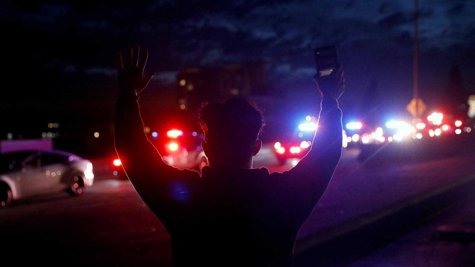Person with back to camera and hands up in surrender, with police cars in background at nighttime