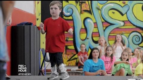 PBS NewsHour -- Kid 'superman,' born with heart defect, radiates strength