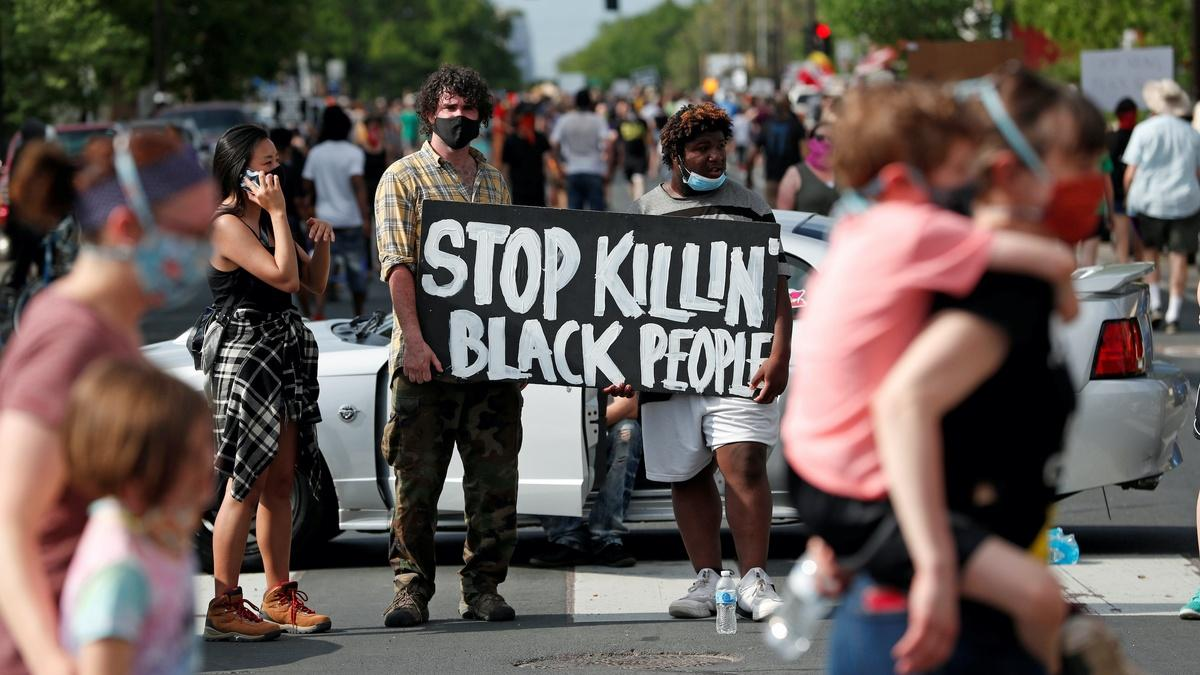 Protesters on street wearing masks; two people with sign that reads 'Stop killin black people'