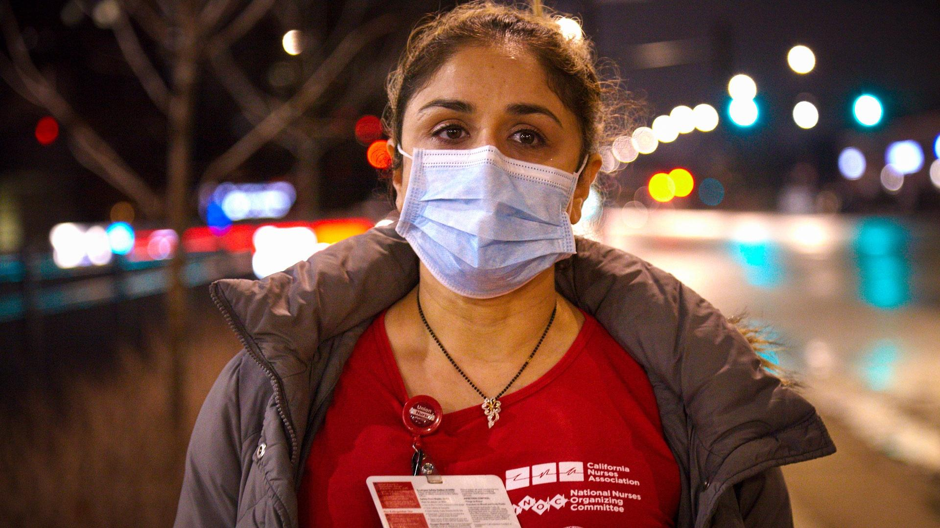 Nurse Falguni Dave on street at night with protective mask on