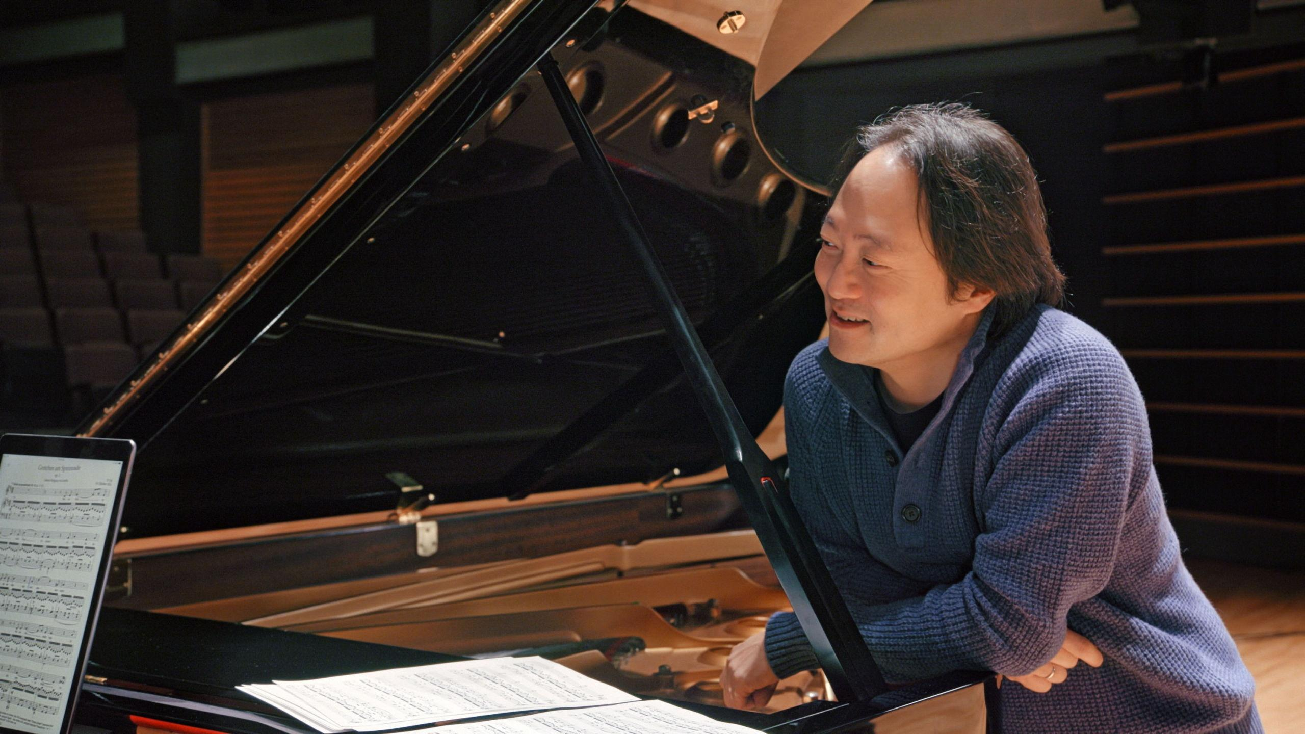 Host Scott Yoo leans over a piano