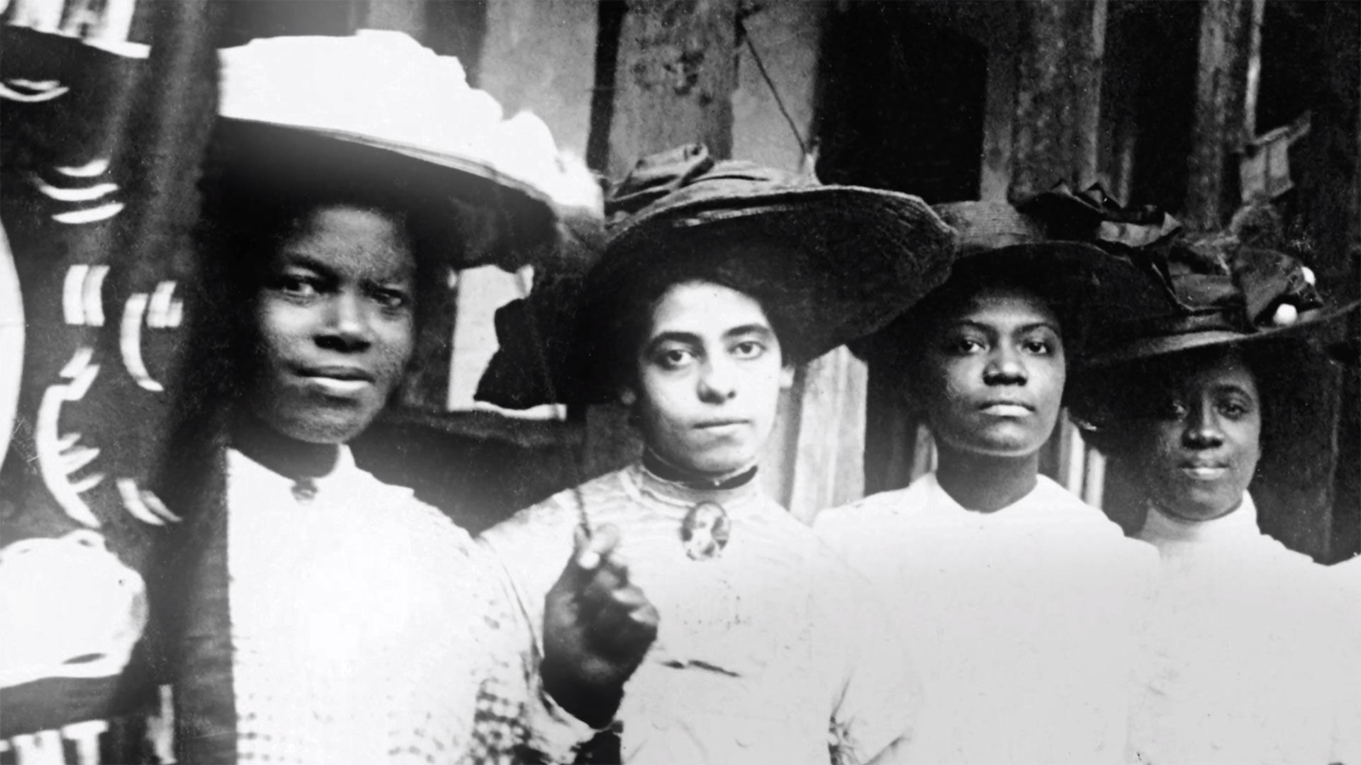 Four women in hats stand side by side