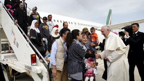 PBS NewsHour -- Refugees' journey ends with a ride on the pope's plane