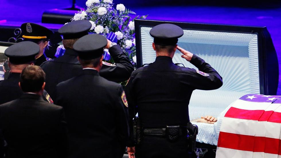 News Wrap: Funerals for slain Dallas police officers begin image