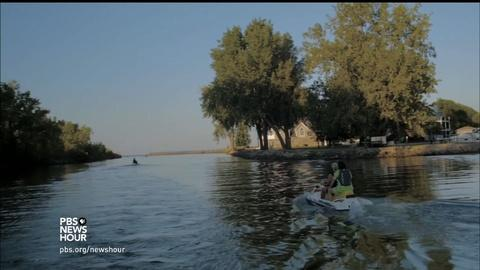 PBS NewsHour -- Who will pay for water cleanup divides urban, rural Iowa