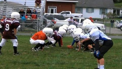 PBS NewsHour -- Young Football Players Take Big-League Hits to Head