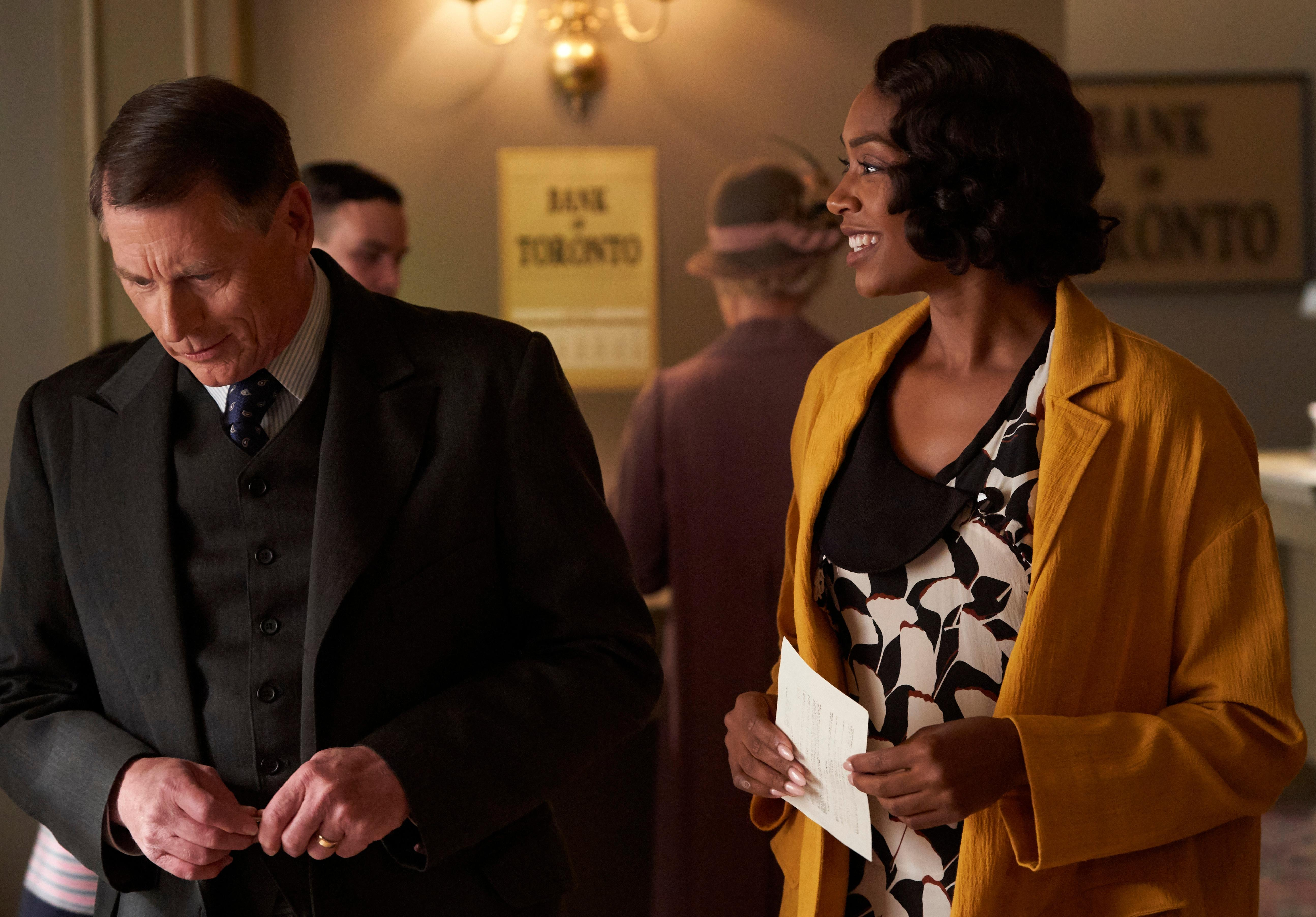 Detective Drake stands next to a woman holding a piece of paper